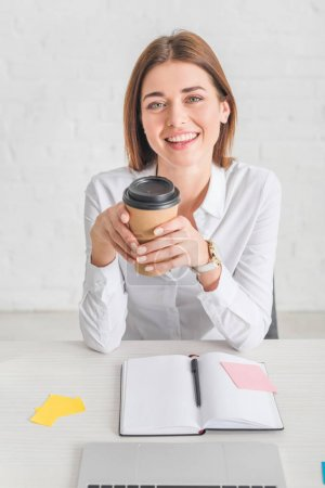 Photo for Happy businesswoman looking at camera and holding paper cup - Royalty Free Image