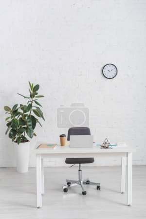 Photo for Modern office with laptop on desk near brick wall - Royalty Free Image