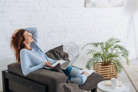 Photo pour Vue latérale de femme heureuse refroidissant avec ordinateur portable à la maison - image libre de droit