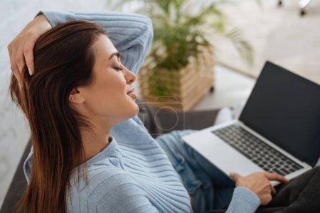 Photo pour Attrayant fille avec les yeux fermés tenant ordinateur portable avec écran vierge à la maison - image libre de droit