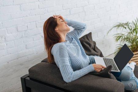 Photo pour Attention petite fille tenant un ordinateur portable avec écran vierge et souriant à la maison - image libre de droit