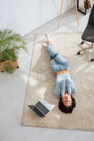 Photo pour Top vue de joyeuse fille glacée sur un tapis près d'un ordinateur portable à la maison - image libre de droit