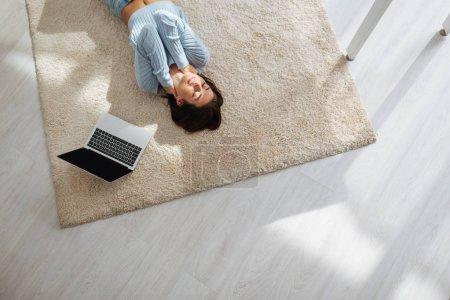 Photo pour Vue de dessus de la femme heureuse se reposant tout en étant couché sur le tapis près d'un ordinateur portable à la maison - image libre de droit