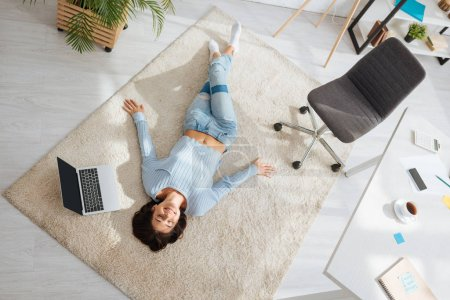 top view of positive woman resting while lying on carpet near laptop at home