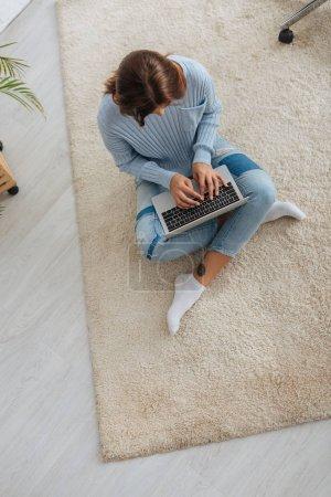 vue du haut du blogueur en utilisant un ordinateur portable tout en étant assis sur le tapis