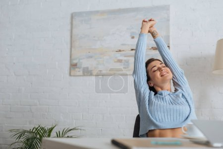 Photo for Selective focus of dreamy girl stretching near table at home - Royalty Free Image
