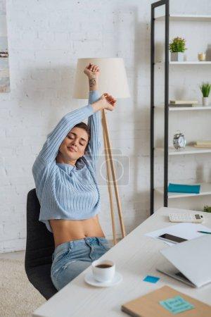 Photo pour Attrayant jeune femme rêvant tout en s'étirant près de gadgets sur la table - image libre de droit