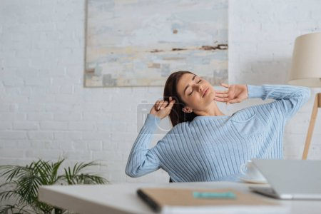 Photo for Selective focus of dreamy woman stretching near table at home - Royalty Free Image