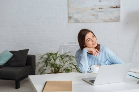 Photo for Dreamy woman looking away near laptop and cup on table - Royalty Free Image