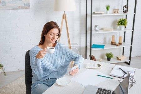Photo pour Heureuse femme utilisant un téléphone intelligent tout en tenant une tasse de café et en se refroidissant à la maison - image libre de droit