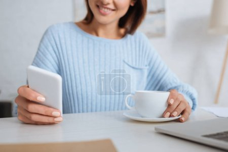 Photo for Cropped view of cheerful woman using smartphone near cup with coffee - Royalty Free Image