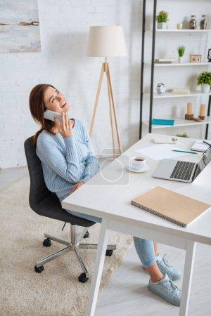Photo pour Joyeuse jeune femme parlant sur smartphone et se refroidissant à la maison - image libre de droit