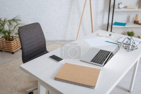 Foto de Laptop cerca de smartphone con pantalla en blanco en la mesa blanca. - Imagen libre de derechos