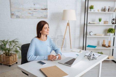 femme heureuse avec tasse de café près de gadgets sur la table