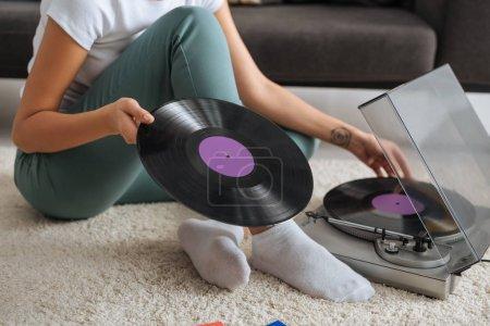 Photo pour Vue recadrée d'une fille tatouée assise sur un tapis et touchant disque vinyle près d'un tourne-disque rétro - image libre de droit