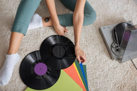 Photo for Cropped view of tattooed woman sitting near retro vinyl player - Royalty Free Image