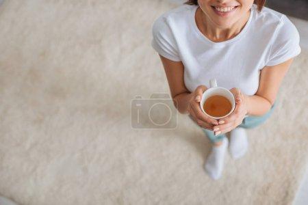 Photo pour Vue recadrée de fille heureuse tenant tasse avec thé - image libre de droit