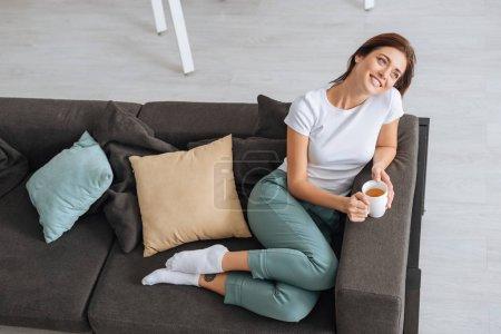 Photo pour Vue aérienne de fille rêveuse refroidissant le canapé avec une tasse de thé - image libre de droit