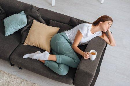 Photo pour Vue aérienne d'une femme séduisante Réfrigération d'un canapé avec une tasse de thé - image libre de droit