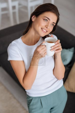 Photo pour Attrayant femme rêvant et tenant tasse de thé - image libre de droit
