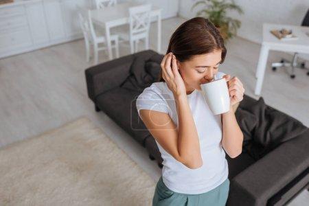 Photo pour Vue aérienne de la jeune femme buvant du thé dans le salon - image libre de droit