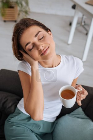 Photo for Young dreamy woman holding cup with tea while chilling on sofa in living room - Royalty Free Image