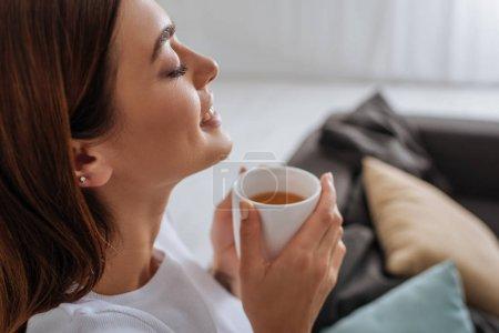 Photo pour Vue latérale de la femme attrayante tenant tasse avec thé - image libre de droit