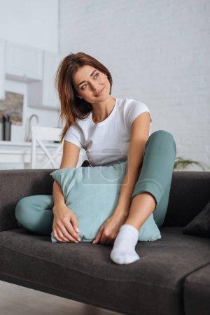 verträumtes Mädchen schaut weg, während es sich auf dem Sofa mit Kissen entspannt