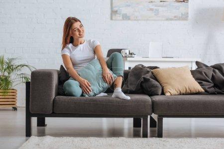 Photo pour Une fille souriante regardant ailleurs tout en relaxant sur un canapé avec oreiller - image libre de droit