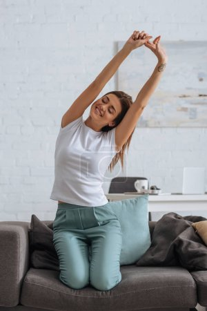 Photo for Smiling woman stretching while chilling on sofa in living room - Royalty Free Image