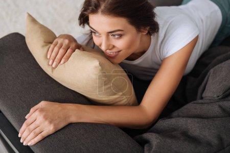 Photo pour Vue aérienne de la femme souriante se refroidissant tout en étant couché sur le canapé près de l'oreiller - image libre de droit