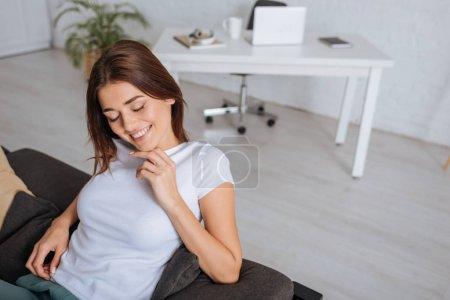 Foto de Mujer joven sonriente con los ojos cerrados relajándose en el salón - Imagen libre de derechos