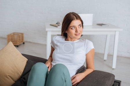 Photo pour Jeune femme rêveuse se détendre dans le salon - image libre de droit