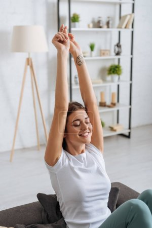 Photo pour Tattooed woman with outstretched hands smiling and relaxing in living room - image libre de droit