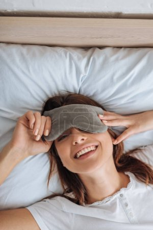 Photo pour Top view of happy young woman in eye mask - image libre de droit