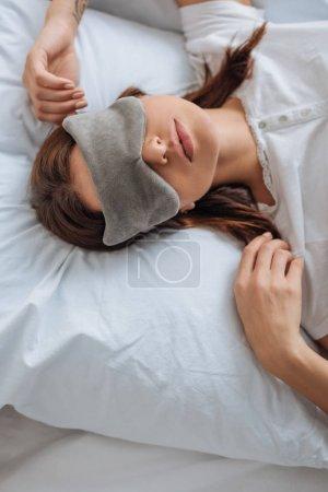 Photo pour Top view of young woman in eye mask - image libre de droit