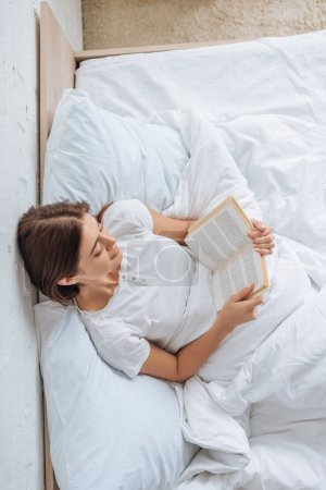 Photo for Top view of happy girl reading book while chilling in bed - Royalty Free Image