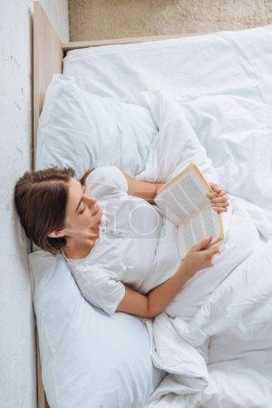 Photo pour Vue du haut du livre de lecture fille heureuse tout en refroidissant au lit - image libre de droit