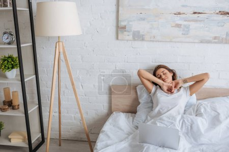 Photo for Dreamy woman chilling in bed near laptop - Royalty Free Image