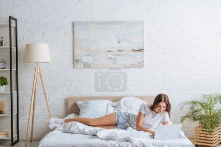 Photo pour Femme heureuse utilisant un ordinateur portable tout en se relaxant dans la chambre - image libre de droit