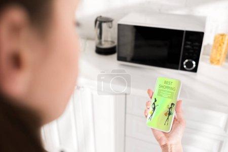 Photo pour Focalisation sélective de la femme tenant un smartphone avec la meilleure application d'achat et micro-ondes à l'arrière-plan - image libre de droit
