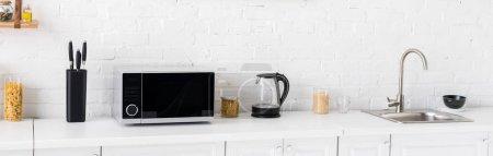 Photo pour Photo panoramique de micro-ondes, bouilloire électrique, pâtes, couteaux et évier dans la cuisine - image libre de droit
