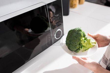 Photo pour Vue recadrée de la femme tenant la plaque avec brocoli près micro-ondes - image libre de droit