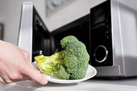 Photo for Cropped view of woman holding plate with broccoli near microwave - Royalty Free Image