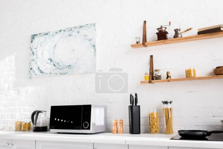 Photo for Microwave, electric kettle, pasta, knives, pepper mill, salt mill on surface in kitchen - Royalty Free Image