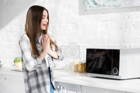 Photo pour Femme souriante et attrayante avec des mains priantes regardant micro-ondes dans la cuisine - image libre de droit