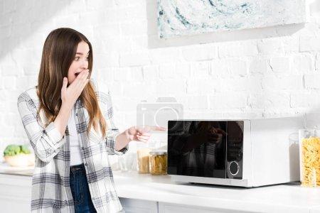 Photo pour Femme choquée et séduisante pointant du doigt au micro-ondes dans la cuisine - image libre de droit