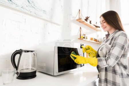 smiling woman in rubber gloves cleaning microwave with sponge