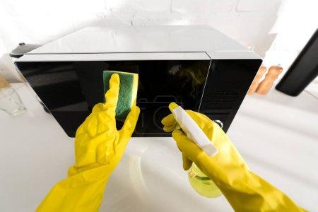 Photo pour Vue recadrée de la femme en gants de caoutchouc nettoyage micro-ondes avec éponge - image libre de droit