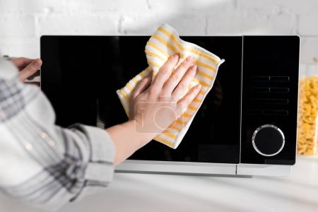 Photo for Cropped view of woman cleaning microwave with rag in kitchen - Royalty Free Image